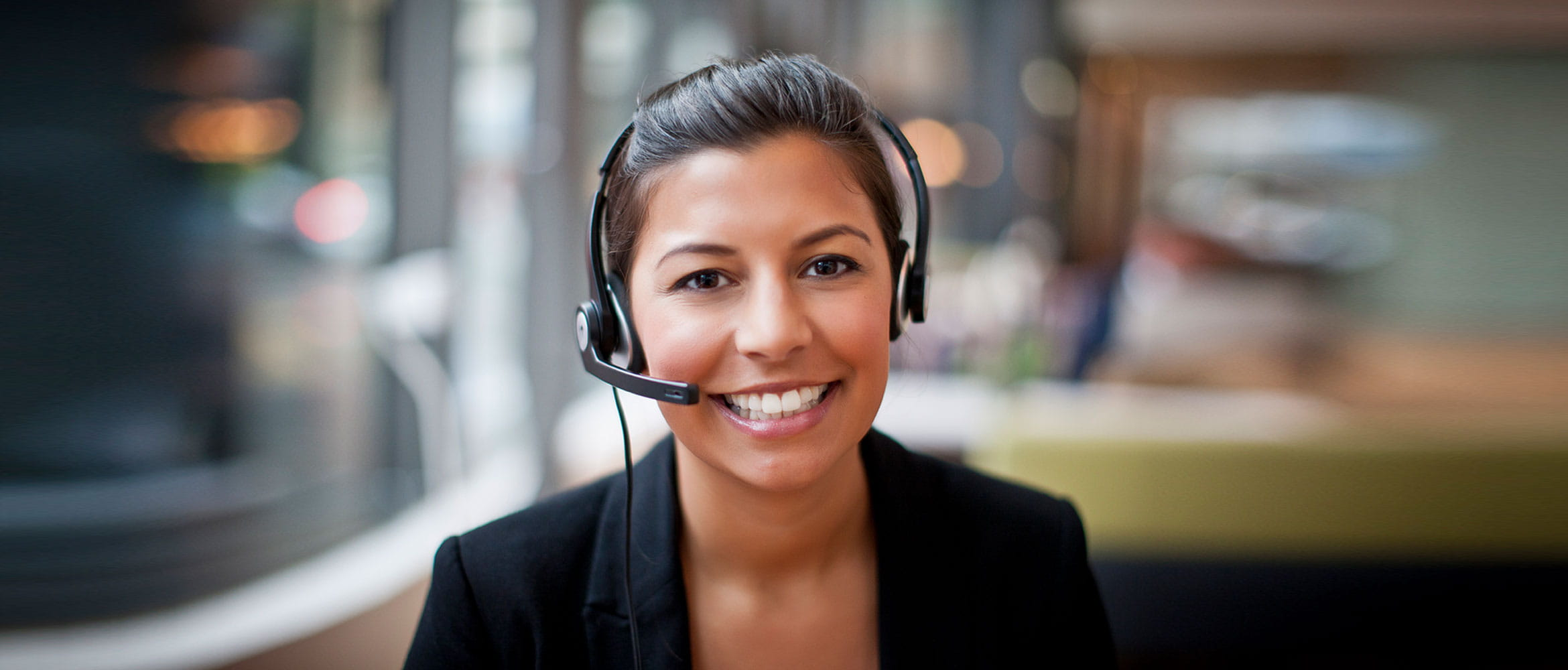 Smiling lady wearing a hands free headset looks at the camera