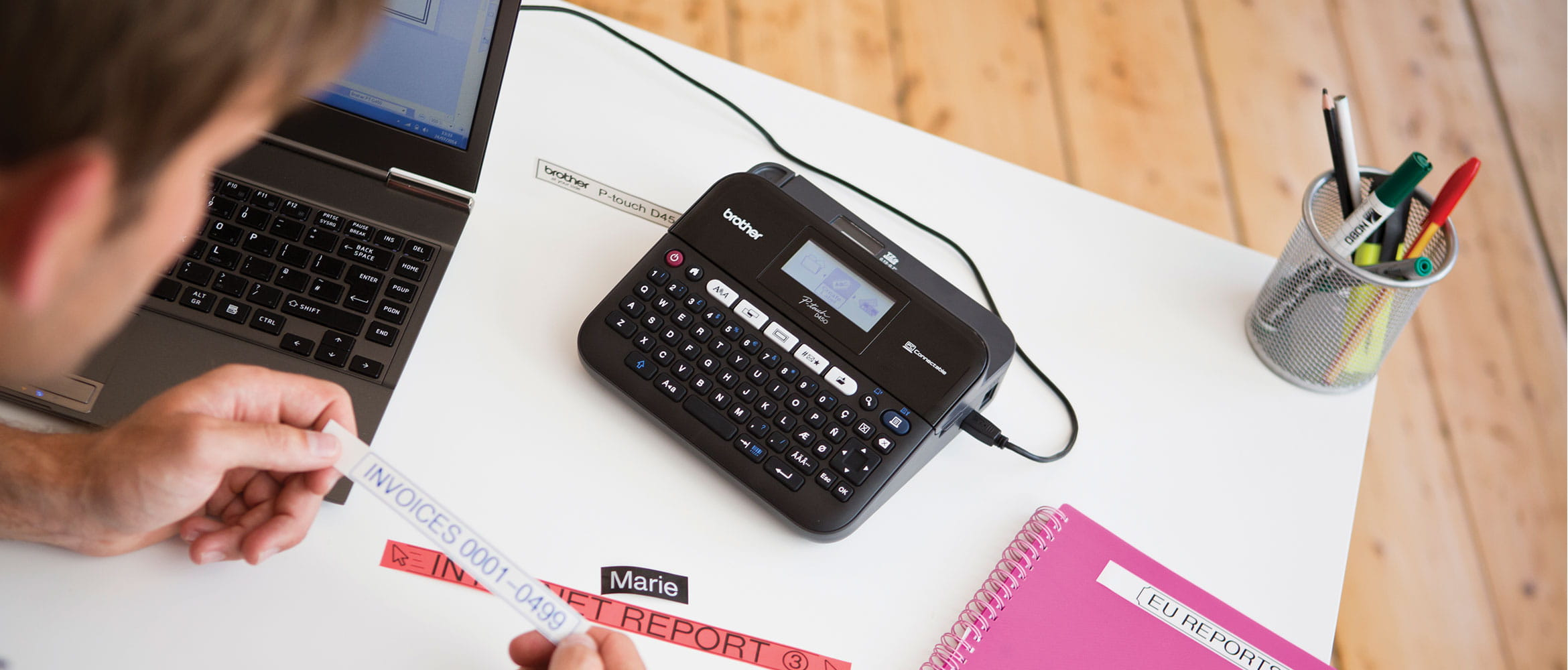 Man using Brother label printer to label invoices at his desk
