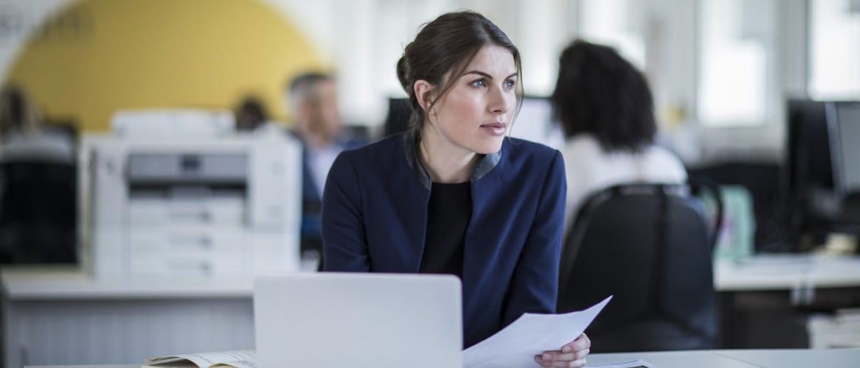 Une femme travaillant sur son ordinateur portable est assise à un bureau avec une imprimante Brother en arrière-plan.