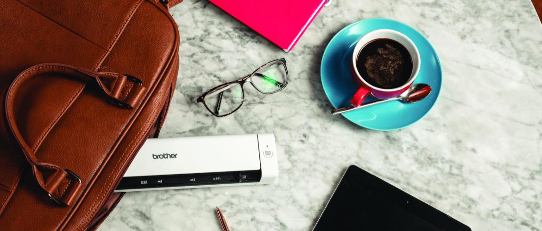 Plusieurs objets sont posés sur une table en marbre, parmis eux des lunettes de vue, une tasse à café turquoise et une sacoche de laquelle dépasse un scanner portable Brother.