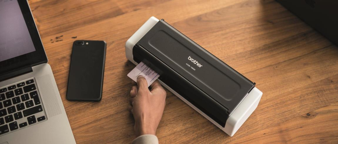 Un scanner de documents Brother posé à côté d'un téléphone portable et d'un ordinateur