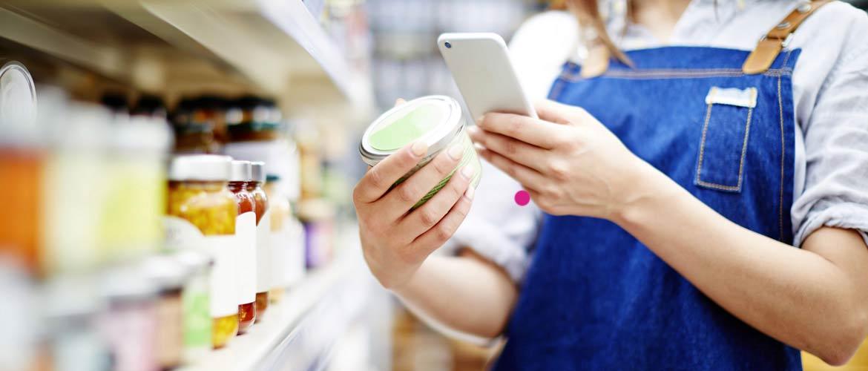Femme scannant une boîte de conserve avec son smartphone