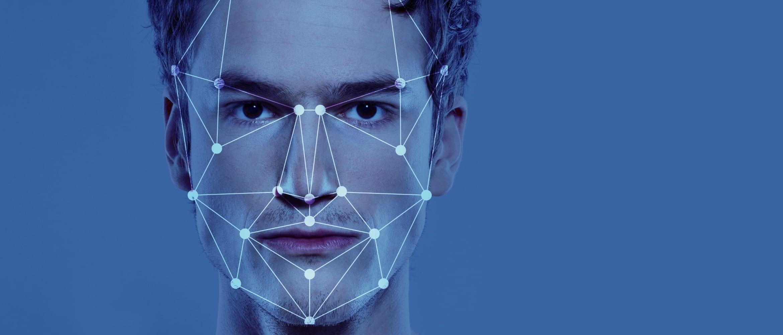 Contour graphique de reconnaissance faciale superposé sur le visage d'un jeune homme sur un fond bleu
