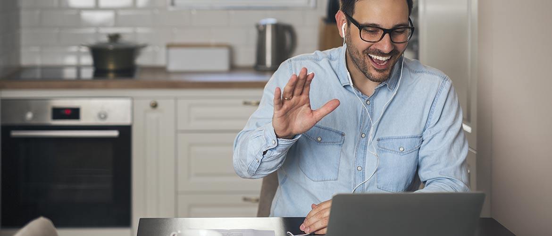 Un homme en télétravail dans sa cuisine salue un collègue d'un geste de la main via son ordinateur