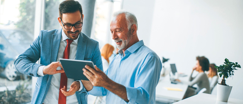 Un jeune homme vêtu d'une combinaison lumineuse et un collègue plus âgé, vêtu d'une chemise plus décontractée, discutent d'un projet d'entreprise sur une tablette lors d'une réunion informelle dans le lieu de travail le plus diversifié et le plus collaboratif du futur