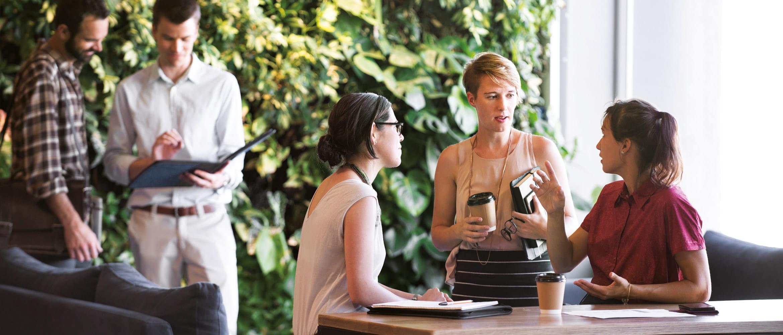 Deux hommes et trois femmes organisent une réunion de travail informelle sur le lieu de travail du futur, qui met en vedette un mur végétal en premier plan dans l'environnement de bureau.