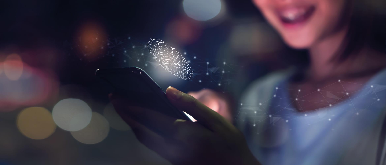 Une jeune femme souriante se connecte à son téléphone professionnel en utilisant ses empreintes digitales.