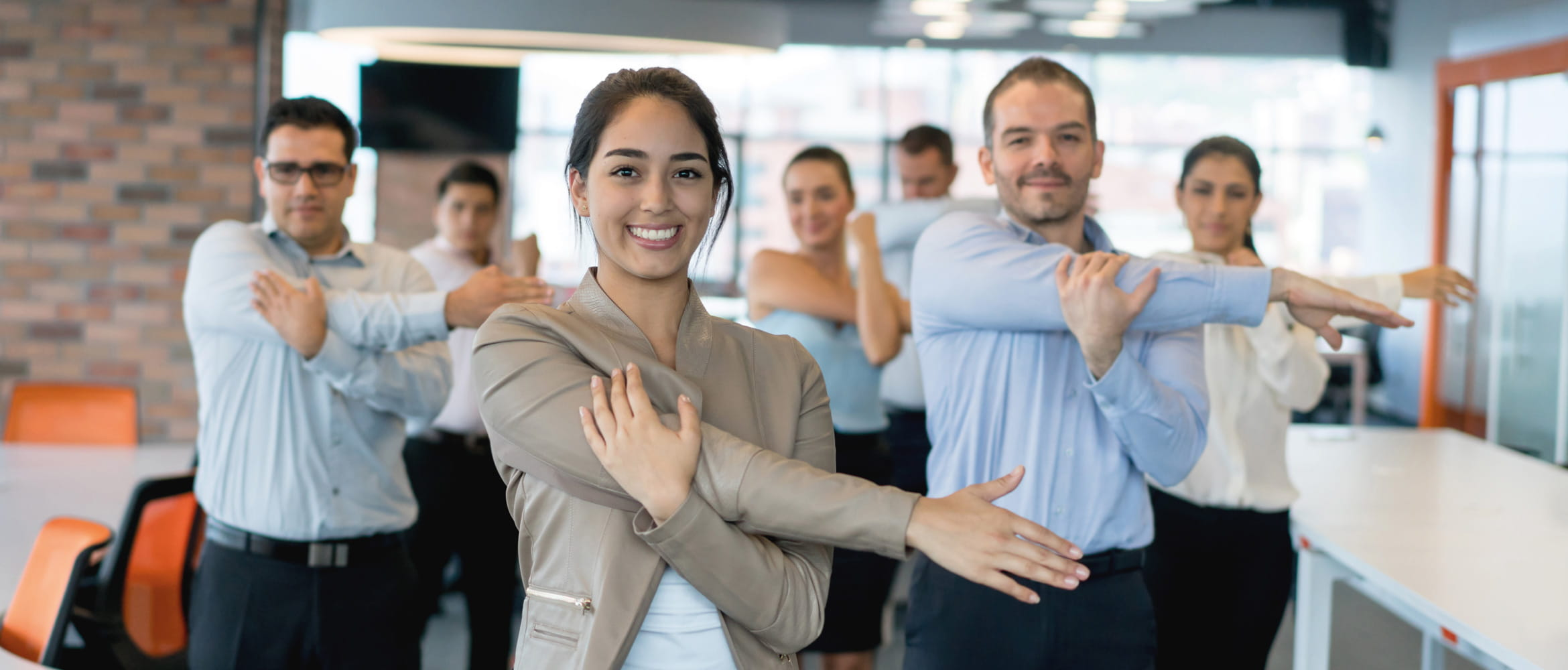 Seven office co-workers take time out to focus on fitness and wellbeing by doing some stretching exercises together in the workplace of the future