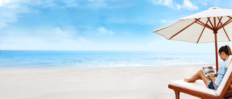 Femme allongée sur un transat en bois sur la plage travaillant sur son ordinateur portable