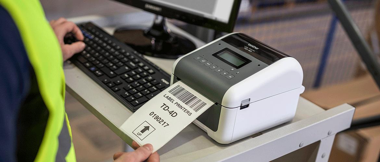 Homme prenant l'étiquette de l'imprimante d'étiquettes Brother TD-4D sur un bureau avec un écran d'ordinateur et un clavier