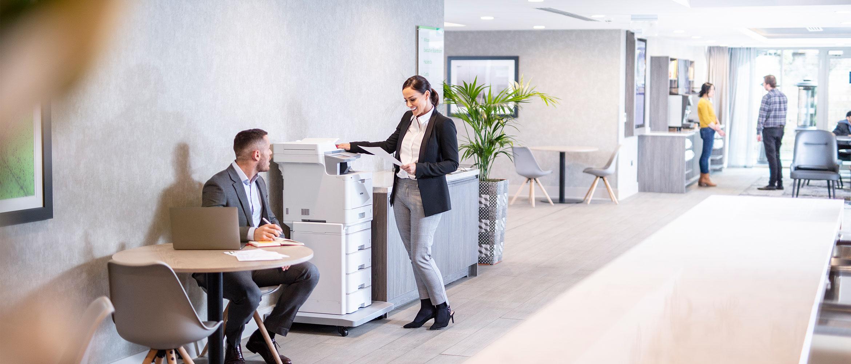 Une femme en costume se tenait devant une imprimante laser couleur Brother MFC-L9570CDWTT et un homme en costume est assis à la table d'à côté avec un ordinateur portable, des plantes, des gens au fond