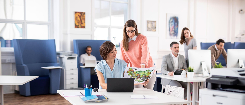 Un bureau occupé avec du personnel sur des ordinateurs portables