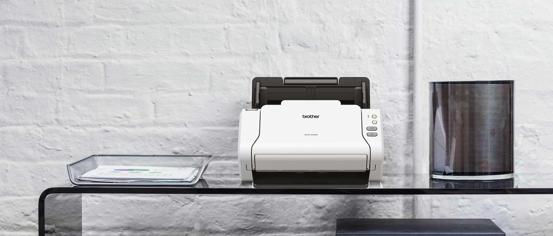 Scanner de bureau Brother ADS-2200 posée sur table en verre avec bord incurvé, plateau en papier métallique