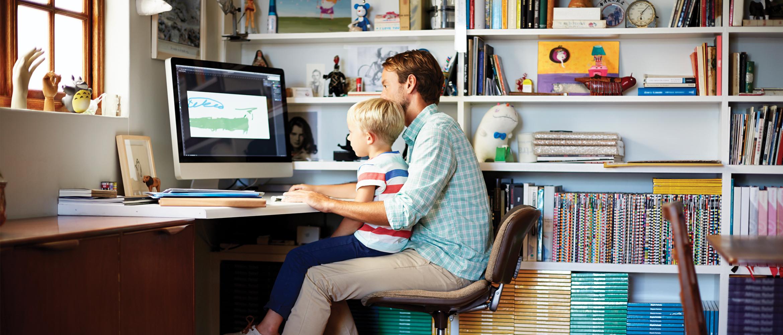 Un homme en situation de télétravail est assis, et regarde un écran d'ordinateur avec un enfant assis sur ses genoux.