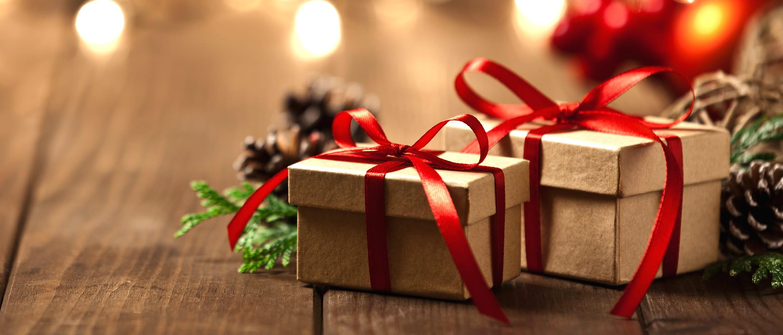 Cadeaux de Noël fermés par un ruban de satin rouge entre des pommes de pin