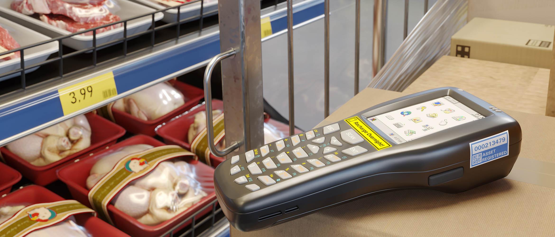 Etiquetage de codes-barres de produits alimenataires avec des étiquettes TZE de Brother. Le lecteur de codes-barres est posé sur une étagère devant le rayon.