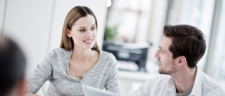 Un homme et une femme devant un ordinateur portable sourient, une imprimante en arrière-plan