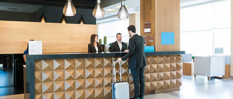 Femme au restaurant ou à la réception de l'hôtel, escaliers, tables, chaises