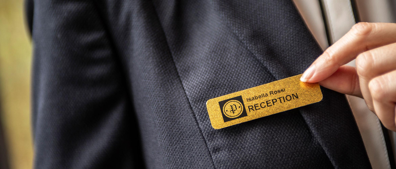 Réceptionniste d'hôtel portant un badge nominatif sur une étiquette noir sur or à paillettes