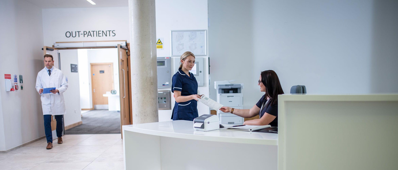 Réceptionniste portant des lunettes assise au bureau des admissions où une imprimante Brother y est posé. Une infirmière tend un dossier à la réceptionniste tandis qu'un médecin passe en arrière plan.