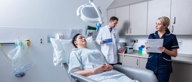 Une patiente allongée dans la salle d'auscultation avec une infirmière notant les informations recueillies sur un formulaire. En arrière plan, l'homme médecin attend que l'étiquette Brother soit imprimée pour rejoindre la patiente..