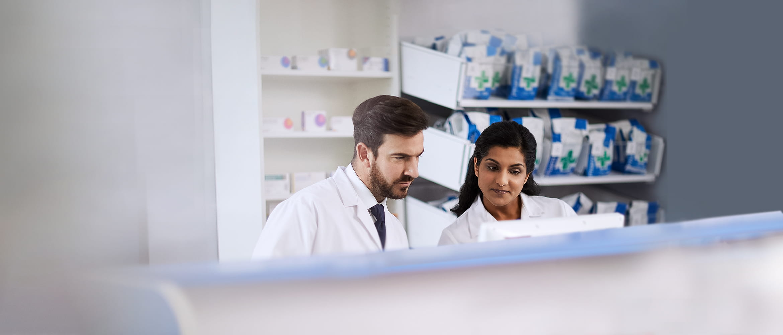 Deux pharmaciens analysent leurs stocks sur leur écran d'ordinateur.