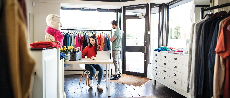Un homme dans un magasin regardant les vêtements et la vendeuse assise en train d'attendre la fin de son impression réalisée par une imprimante Brother.