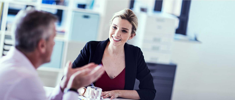 Un homme et une femme assis autour d'une table de réunion entrain de discuter avec en arrière plan une imprimante multifonction Brother