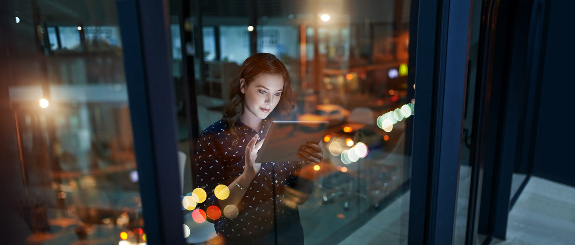 A female office employee is working late in the workplace of the future. She is reviewing a document on her tablet computer while standing next to a window overlooking the city at night.