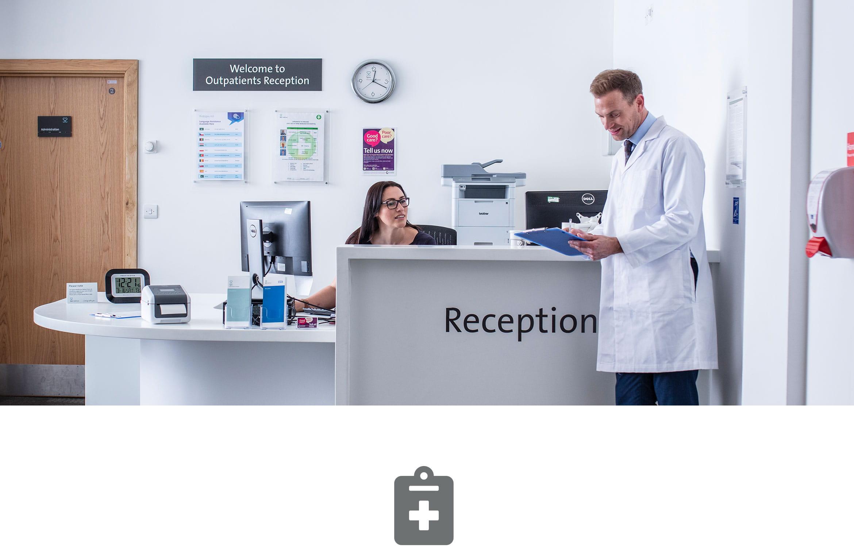 Réception de l'hôpital avec la réceptionniste parlant au médecin en blouse blanche avec en fond une imprimante Brother