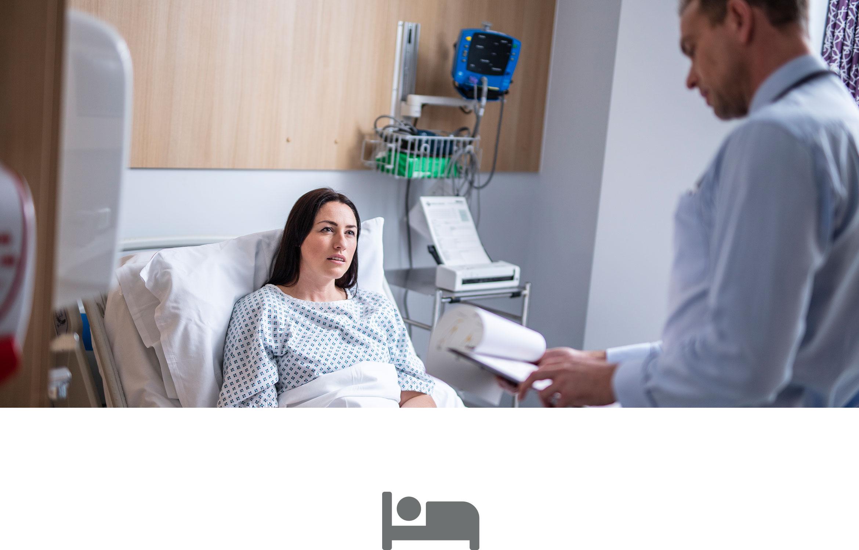 Médecin lisant les résultats d'examen à une patiente assise sur son lit d'hôpital