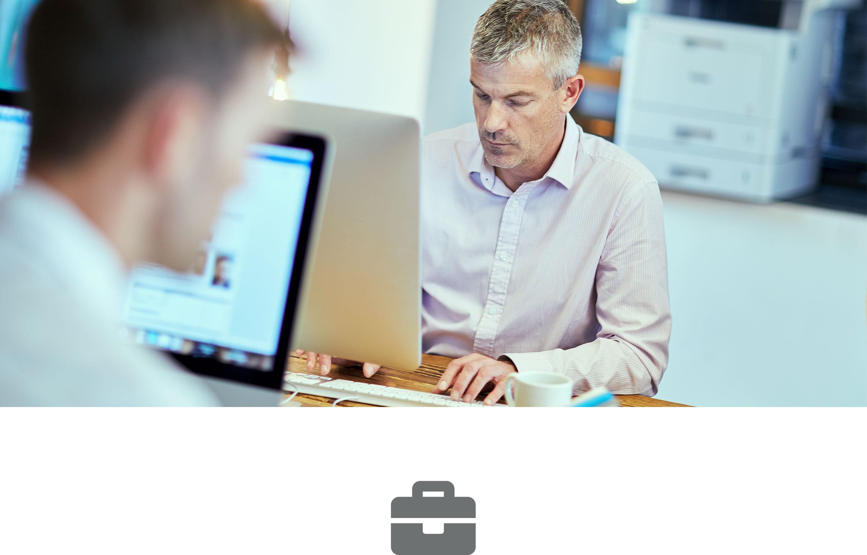 Deux hommes assis à un bureau travaillant sur des ordinateurs avec une imprimante laser en arrière-plan
