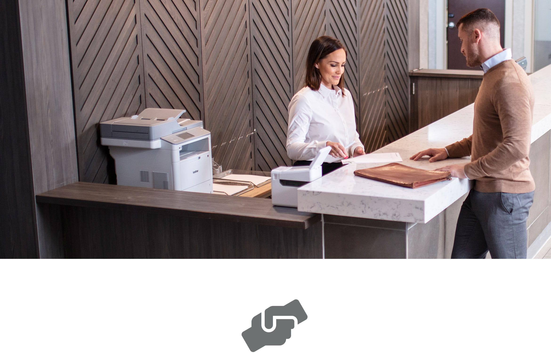 Le client d'un hôtel reçoit l'aide du la réception. Une imprimante laser et d'étiquettes sont présentes sur le comptoir.