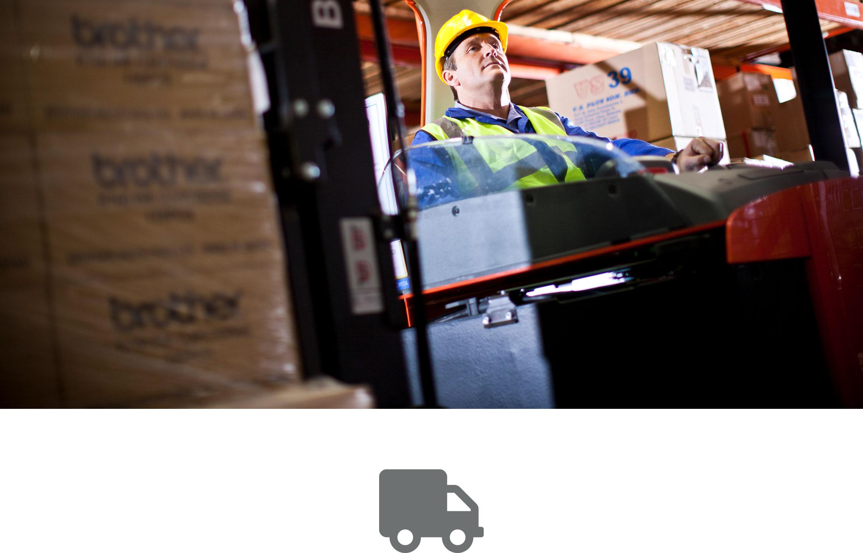 Homme avec un gilet jaune et un casque de sécurité sur un chariot élévateur dans un entrepôt.