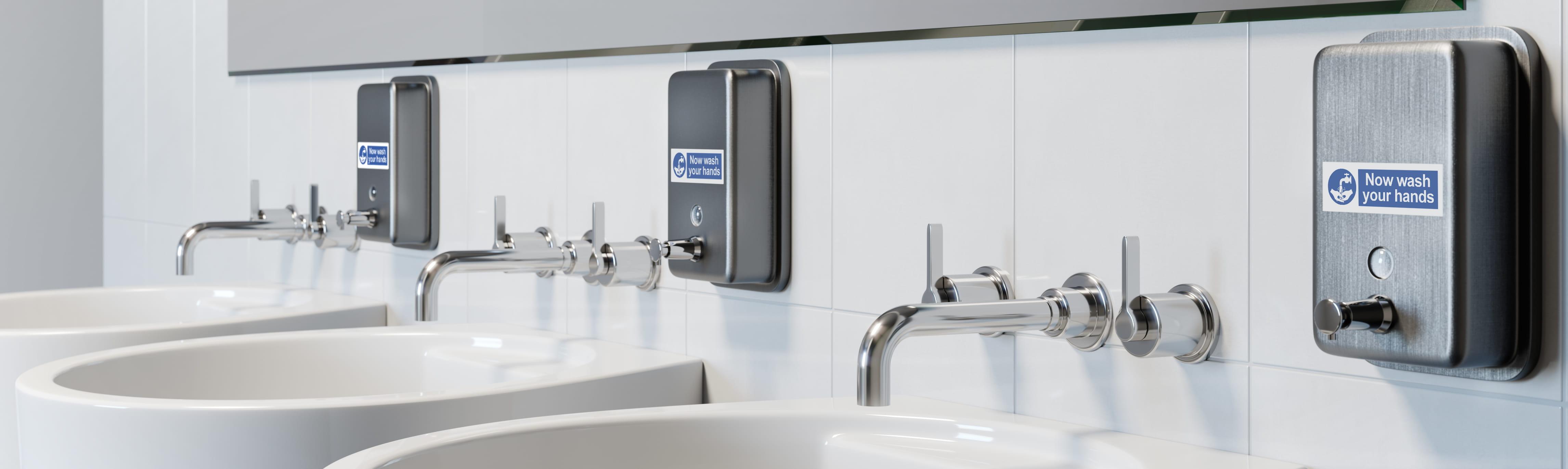 Trois lavabos dans des toilettes partagés avec des étiquettes P-touch Brother collées sur le poussoir à savon
