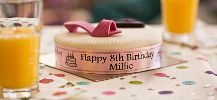 Gâteau d'anniversaire glacé avec ruban autour posé sur la table avec une nappe à pois, jus d'orange, verres