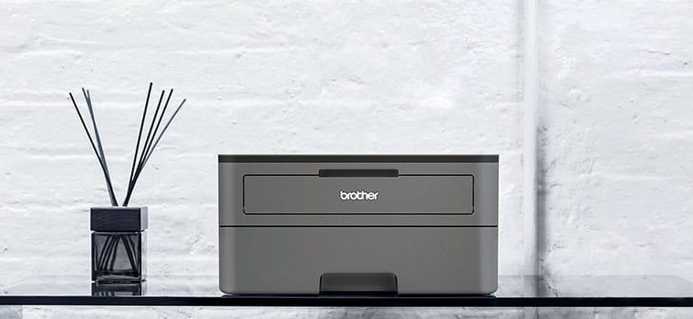 Imprimante laser gris foncé mono HL-2350DW sur une table en verre avec diffuseur d'encens