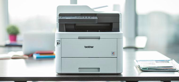 MFC-L3770CDW Imprimante laser couleur multifonctions sur un bureau avec une plante en arrière-plan
