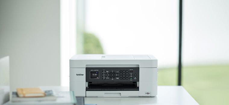 L'imprimante jet d'encre Brother MFC-J497DW posée sur le bureau d'un particulier à son domicile