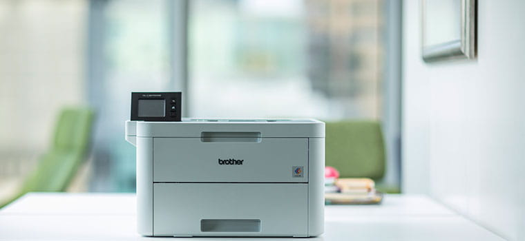 L'imprimante laser Brother HL-L3270CDW posée sur un bureau blanc avec une chaise de bureau verte en arrière-plan