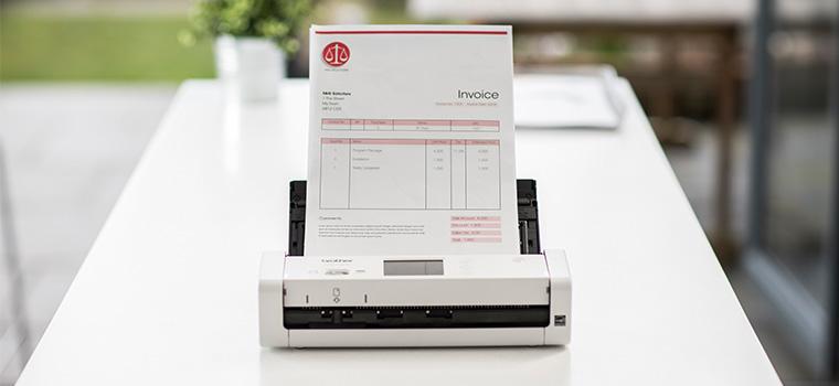 Scanner de documents compact Brother ADS-1700W posé sur un bureau pour scanner un document