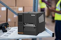 Imprimante d'étiquettes industrielles Brother TJ sur un plan de travail avec des étiquettes imprimées et un scanner dans un entrepôt