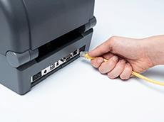 Un câble Ethernet jaune est introduit à la main dans une imprimante TD-4T
