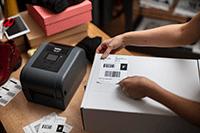 L'imprimante d'étiquettes TD-4T a imprimé une étiquette d'expédition qui est placée sur une boîte blanche