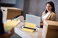 Femme aux cheveux bruns se tenant derrière la réception avec un ordinateur portable utilisant le scanner de documents portable DSmobile DS-740D de Brother avec des boîtes, un livreur