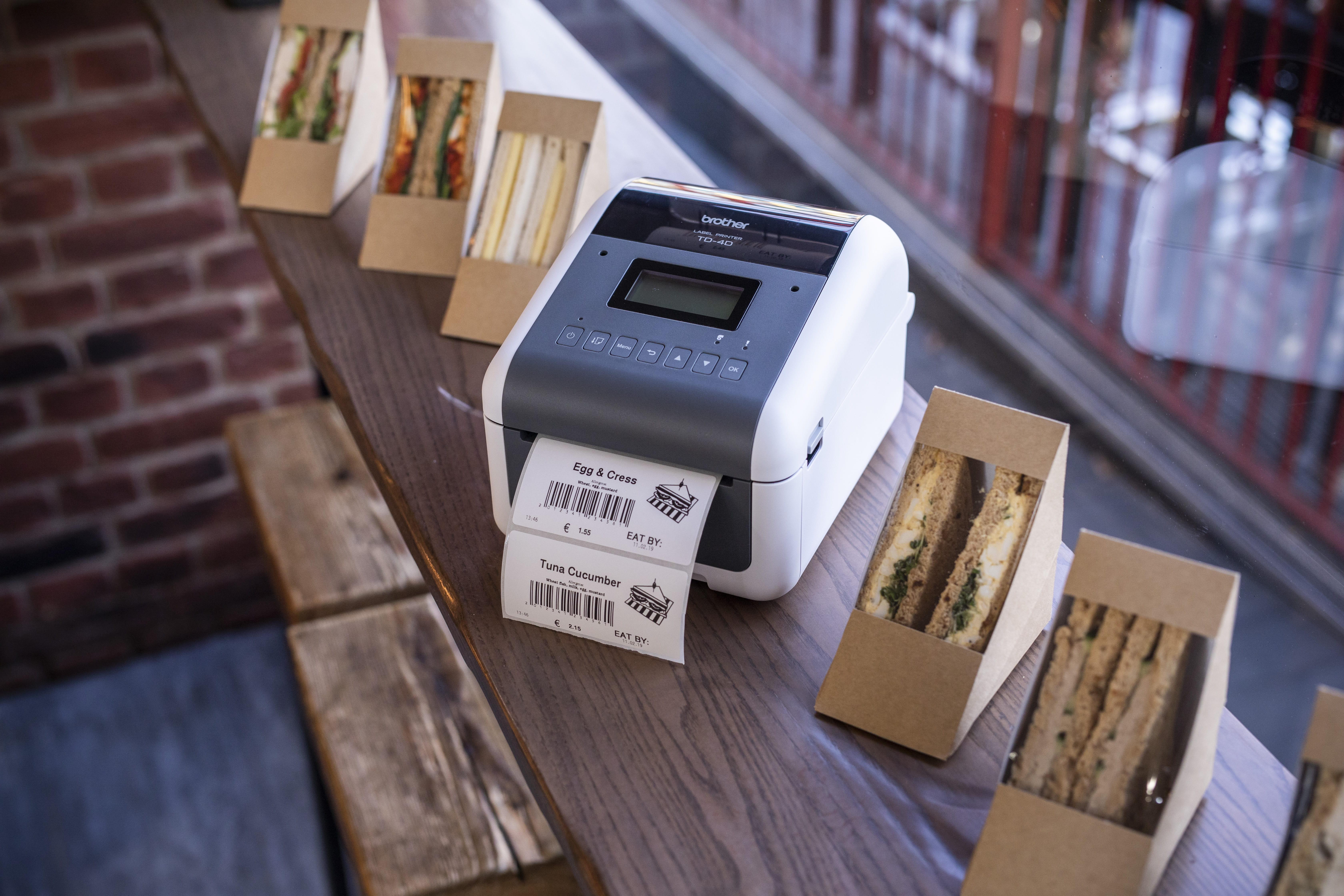 Etiqueteuse TD-4D imprimant une étiquette à coller sur des boîtes à sandwich dans une zone de vente au détail de produits de charcuterie