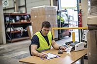 homme en entrepôt avec un ordinateur portable imprimant une étiquette de distribution à partir d'un rouleau continu dans une imprimante d'étiquettes TD4d