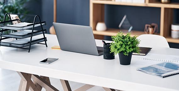 image d'un bureau avec ordinateur portable posé dessus, organiseur de bureau et plante
