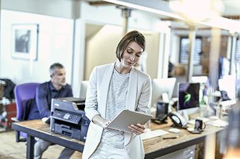 Une femme se tenant près d'une imprimante consulte sa tablette au sein d'un espace de travail partagé.