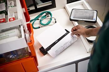 Un professionnel de la santé imprimant un document à l'aide de son imprimante mobile